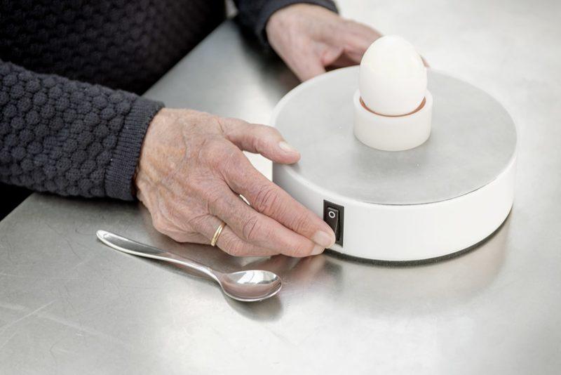 Easy-Up med dug og Easy-Egg sidder på et bord ved siden af en ske. En ældre persons hænder er i fokus i gang med at tænde Easy-Uppen.