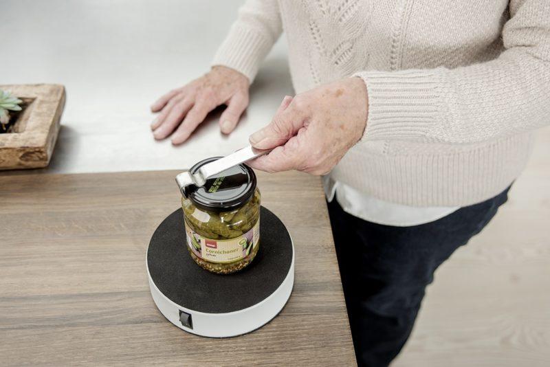 Easy-Release bliver sammen med Easy-Up brugt af en ældre kvinde til at åbne et glas cornichoner.