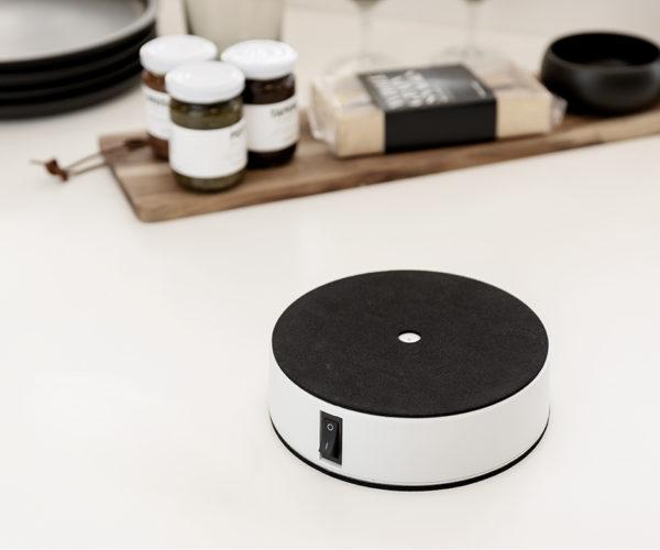 Easy-Up på et bord. Easy-Up er hvid og rund med en sort blød skum top og en sort knap på siden til at tænde og slukke.