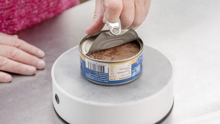 Easy-Up bliver sammen med en beskyttende dug brugt til at åbne en dåse tun med en hånd.