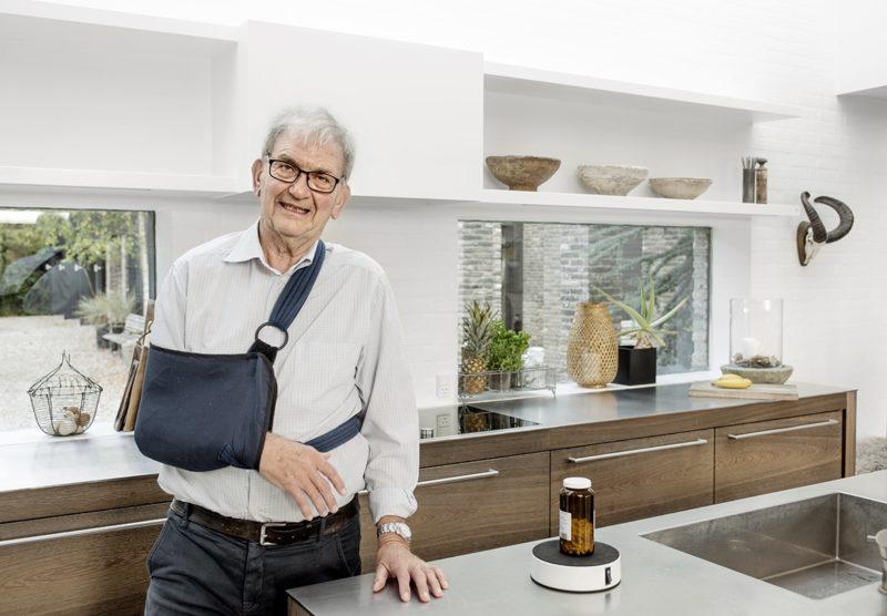 Eigil med arm i slynge ved siden af Easy-Up og pilleglas i køkken.