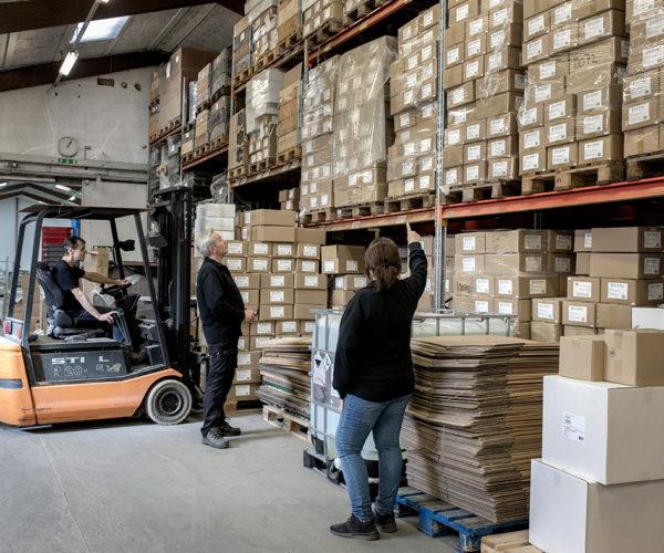 Tre medarbejdere på lageret, hvor én kører gaffeltruck.