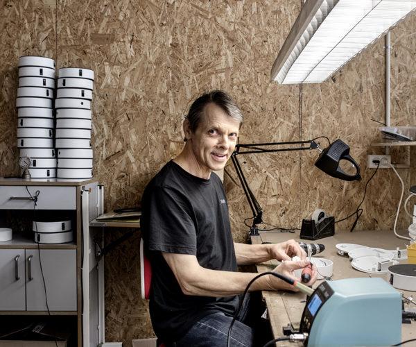 En smilende medarbejder sidder og lodder en Easy-Up. I baggrunden er der en stak med Easy-Up skaller.