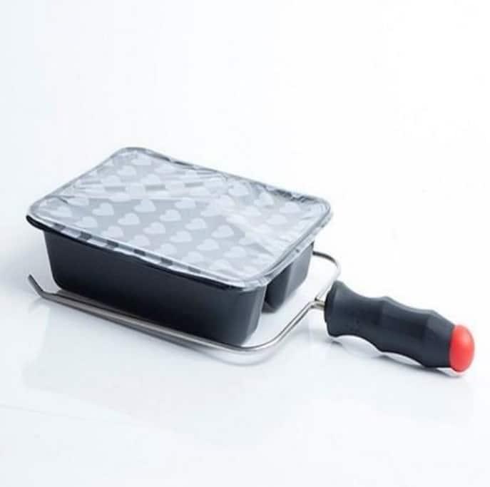 Easy-Grip bakkeholder på hvid baggrund. Bakkeholderen har en stål tang og et sort plastik håndtag med rødt for enden.